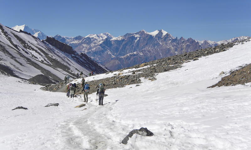Hikers walking on Thorung La pass, Annapurna, Nepal. View from Thorung La pass to Daulagiri mountain. Annapurna trek, Himalaya mountains. Nepal royalty free stock photos