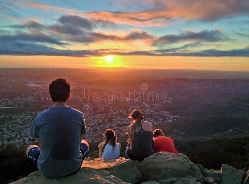 Hikers Watching a Colorful Sunset over San Diego, California. Hikers on Cowles Mountain summit at sunset. Highest peak in the city of San Diego, California royalty free stock images