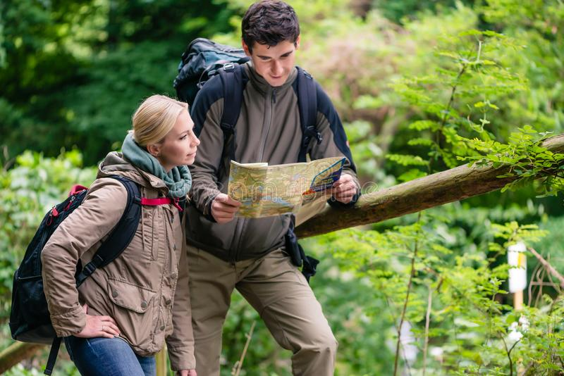 Young hikers orientating with trail map. Hikers, women and man, in the woods orientating with trail map stock photos