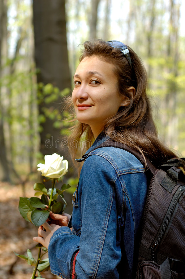 Hiking 1. Young beautiful happy woman hiking in forest with a white rose stock photo