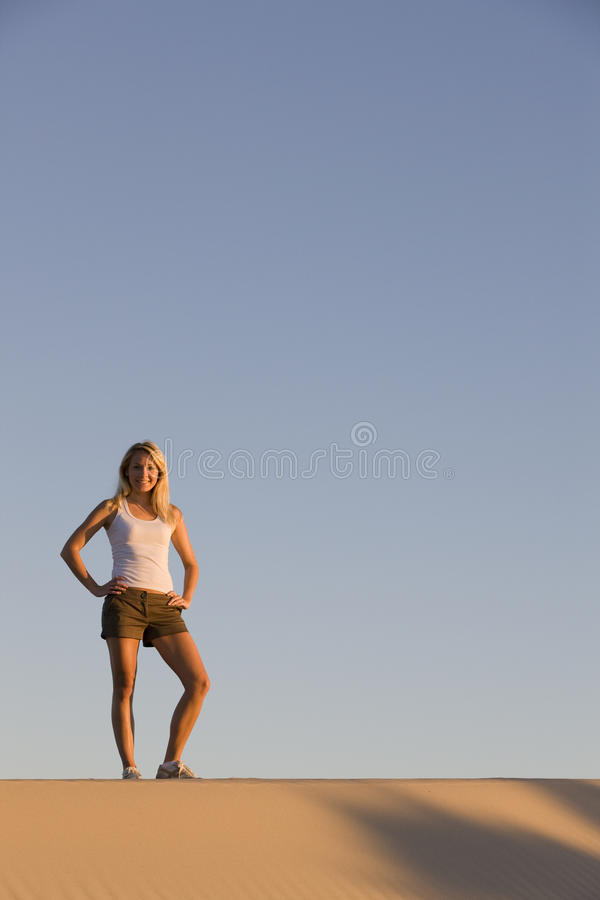Hiking. A beautiful woman standing on a sand dune royalty free stock photo