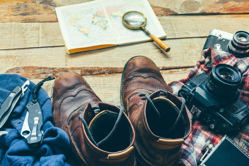 Hiking accessories old leather shoes, shirt, card, vintage film camera and knives concept of adventure and outdoor leisure tourism royalty free stock image