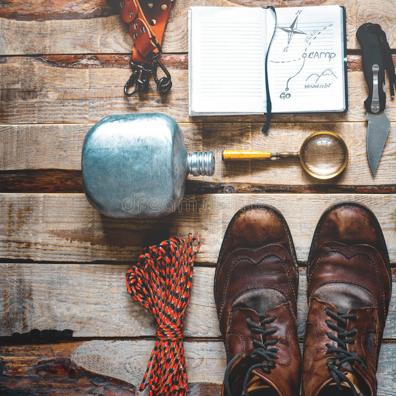 Hiking accessories on wooden background: old hiking leather boots, vintage film camera, travel notebook, knife. Lifestyle concept royalty free stock image