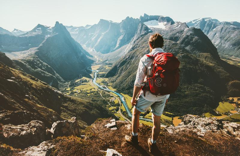 Hiking alone in Norway mountains Man with red backpack. Enjoying landscape on cliff solo traveling healthy lifestyle concept active summer vacations stock image