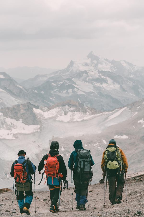 Free Hiking And Climbing. Four Tourists With Backpacks On The Background Of A Mountain Snow-covered Ridge Royalty Free Stock Photography - 157091137