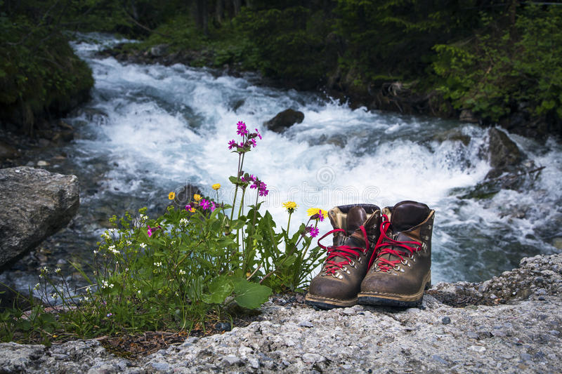 Hiking boots. Old hiking boots near river stock photos