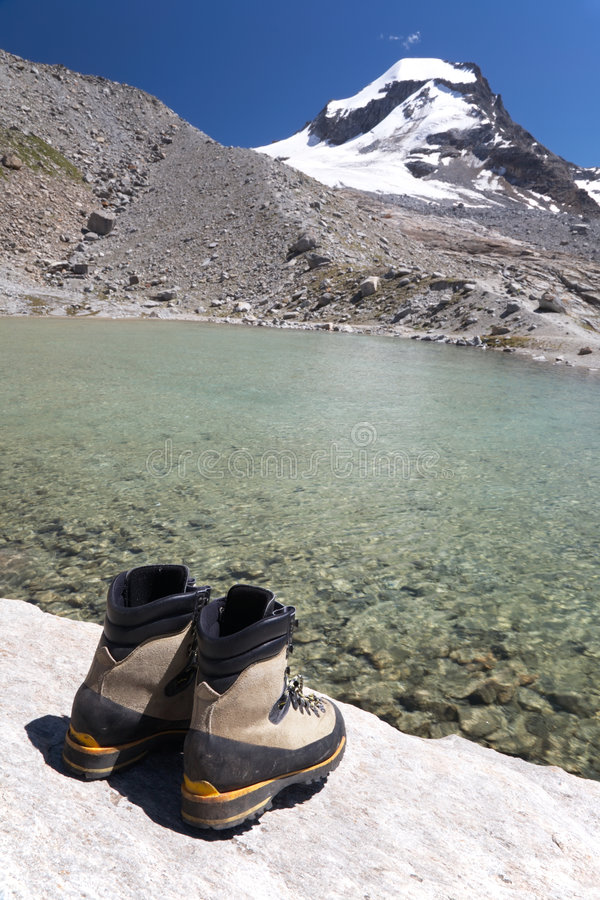 Hiking boots. Back view, in background mountain landscape with lake and snowed peak (Gran Paradiso National Park, Italy stock photography