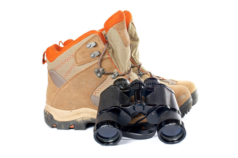 Hiking boots and binoculars. Used hiking boots and binoculars with soft shadow on white background stock photography