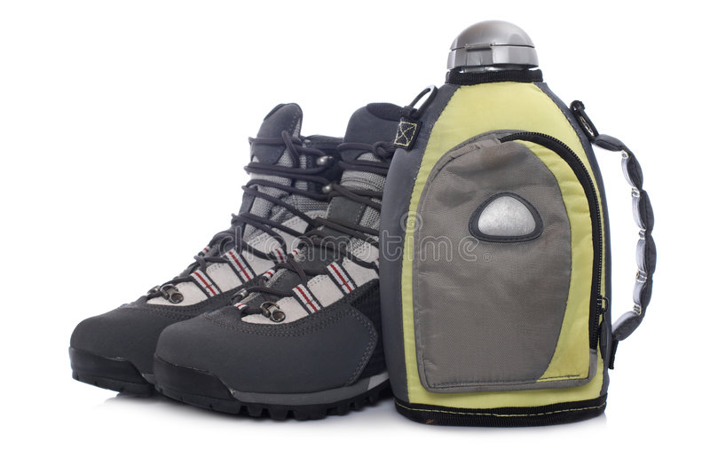 Hiking boots and canteen. A pair of hiking boots and canteen with shadow, reflected on white background royalty free stock images