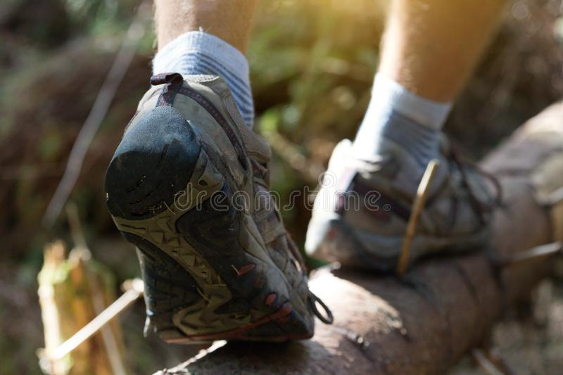 A hiking boots. Hiking boots close-up. boy tourist steps on a log stock photo
