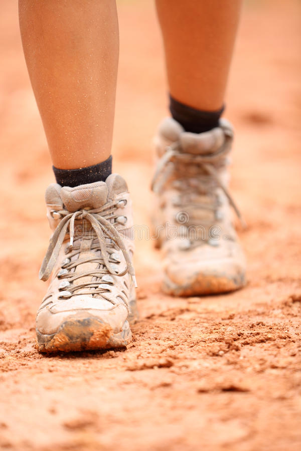 Hiking boots - close up of dirty hiker shoes. Woman feet and female hikers footwear shoe walking on dirt trail hike path outdoor in nature royalty free stock photo