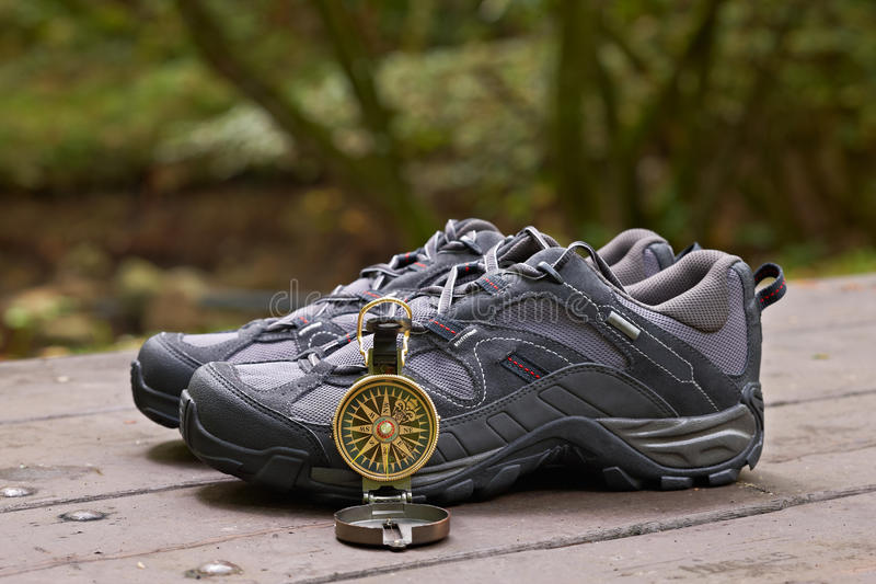 Hiking boots and compass. In the table. Shallow depth of field and blurred background royalty free stock photos