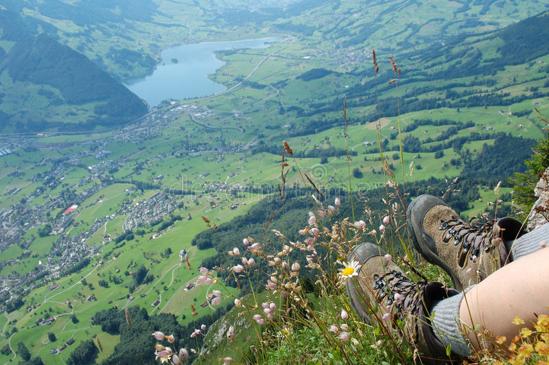 Hiking boots and flowers over a valley royalty free stock images