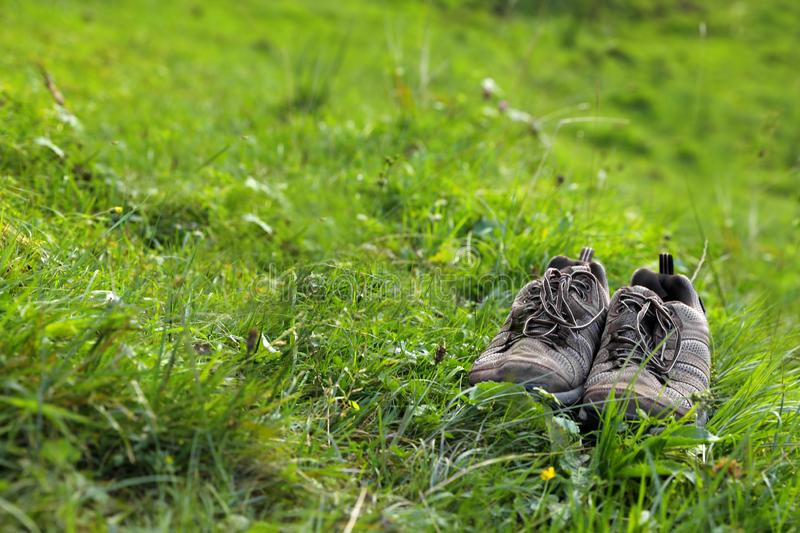 Hiking boots in green mountain valley. Summer camping stock photo