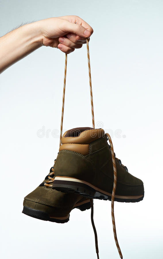 Hiking boots hang on laces. Isolated on white background. Hand hold outdoor shoes on laces stock images