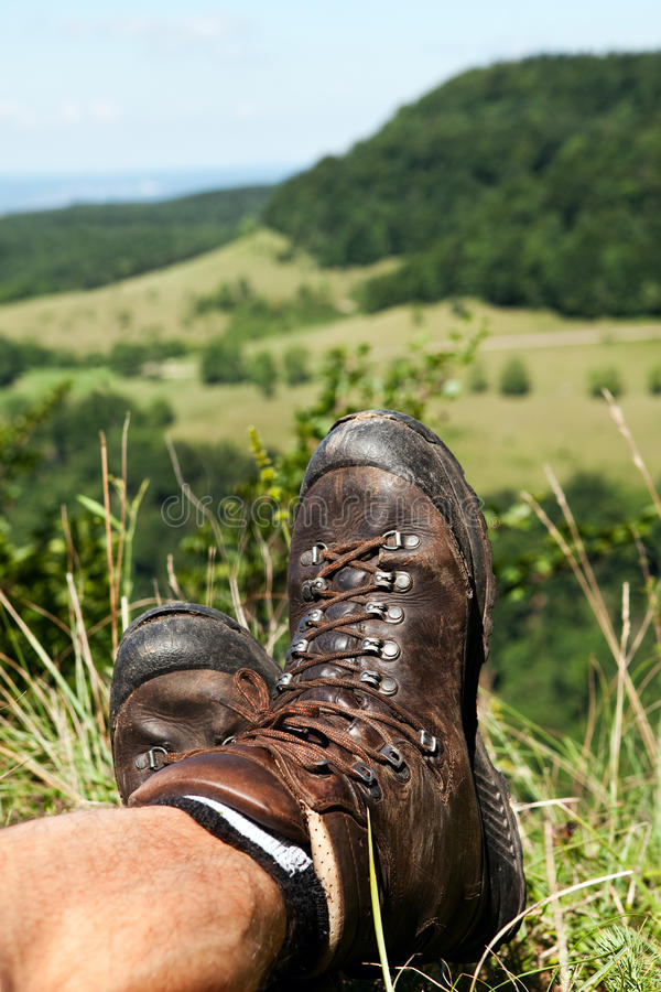 Hiking Boots have a break. Old Hiking boots in a summer meadow from a male Hiker stock photos
