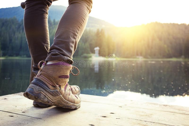 A hiking boots. Hiking boots close-up against the mountain lake synevyr. Carpathians, Ukraine stock photography