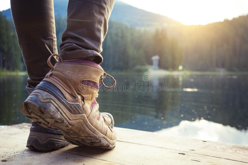 A hiking boots. Hiking boots close-up against the mountain lake synevyr. Carpathians, Ukraine stock image