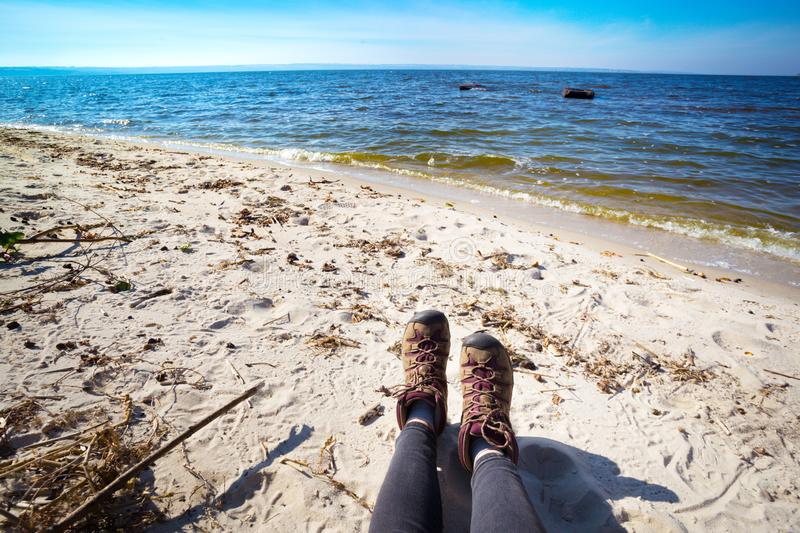 A hiking boots. Hiking boots close-up. girl tourist .resting by the sea royalty free stock image