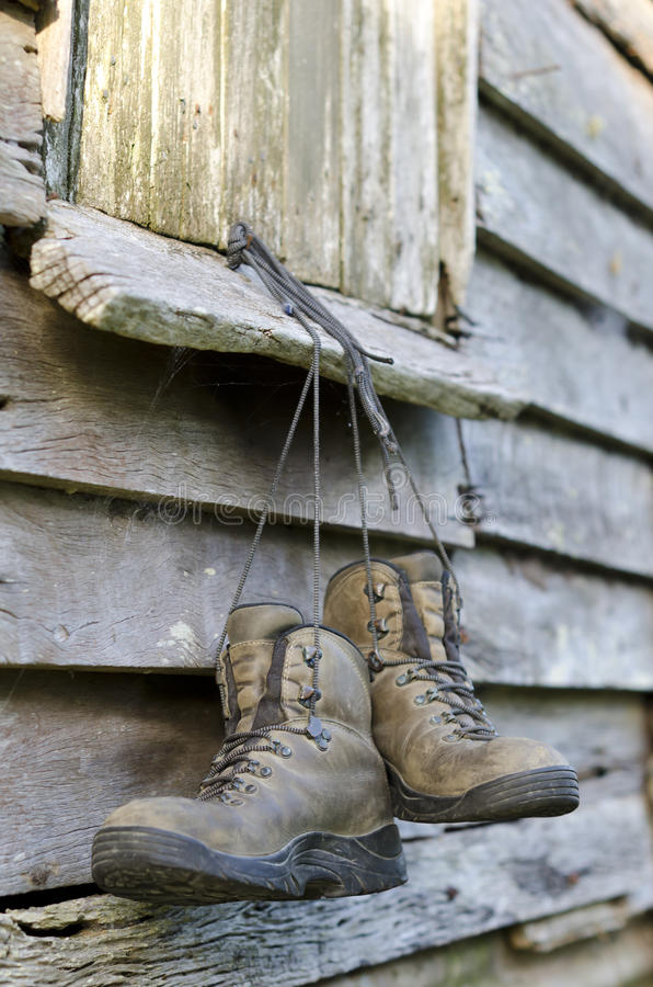 Hiking boots hung from an old barn window. A pair of worn out hiking boots hanging from an old barn window. Barn is made out of old wood. There are also some stock photos