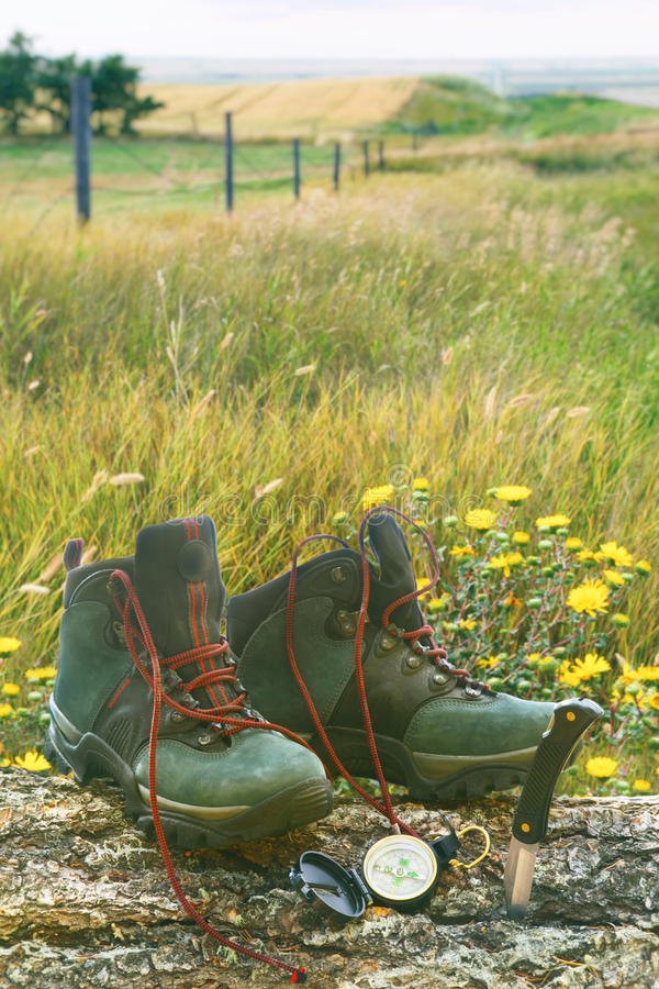 Hiking boots with knife and compass on log in field. Hiking boots with knife and compass on tree log in field of wild flowers stock photography