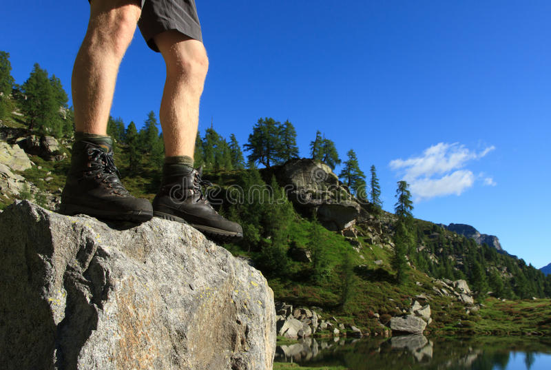 Hiking boots. Man with hiking boots standing on a boulder in the Swiss Alps stock photography