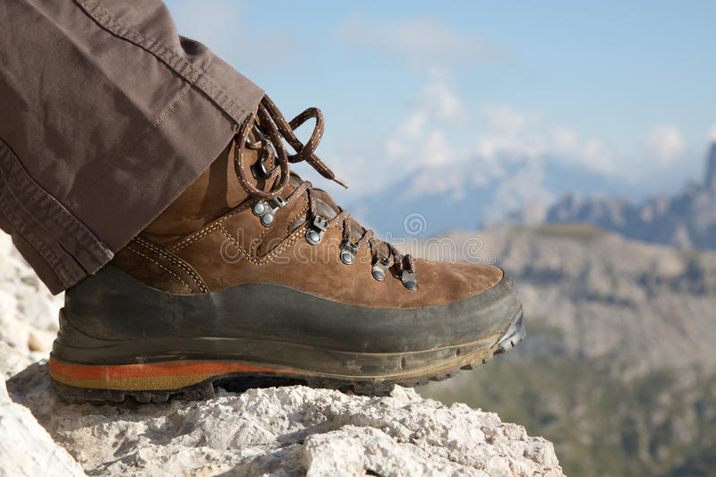 Hiking boots in the mountains. Hiking boots of a hiker on a rock in the mountains royalty free stock photography