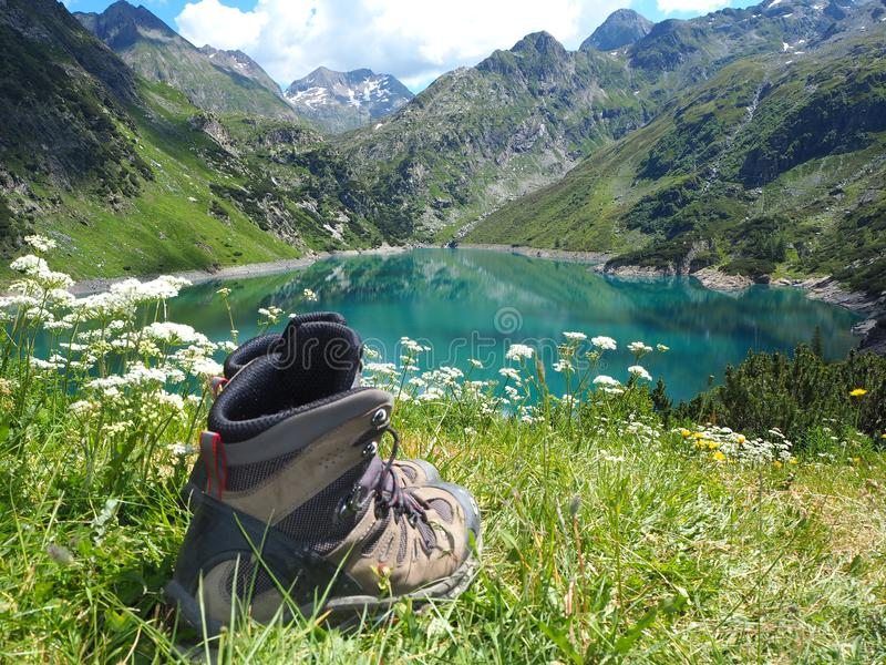 Hiking boots and a natural lake in the background. Italian alps stock image