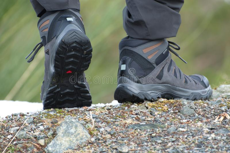 Hiking boots, ready to walk. Edge of rock,stone and snow royalty free stock photo