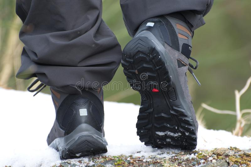 Hiking boots, ready to walk. Edge of rock,stone and snow royalty free stock photos