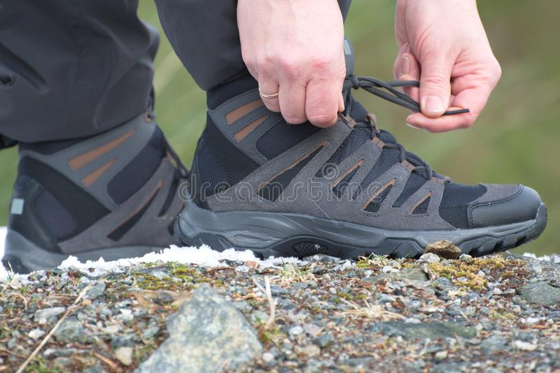 Hiking boots, ready to walk. Edge of rock,stone and snow royalty free stock photography