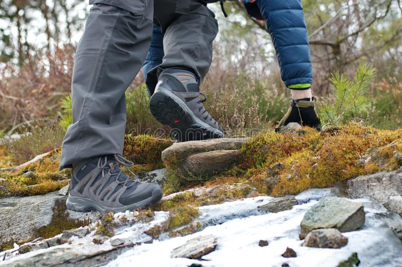 Hiking boots, ready to walk. Edge of rock,stone and snow royalty free stock image