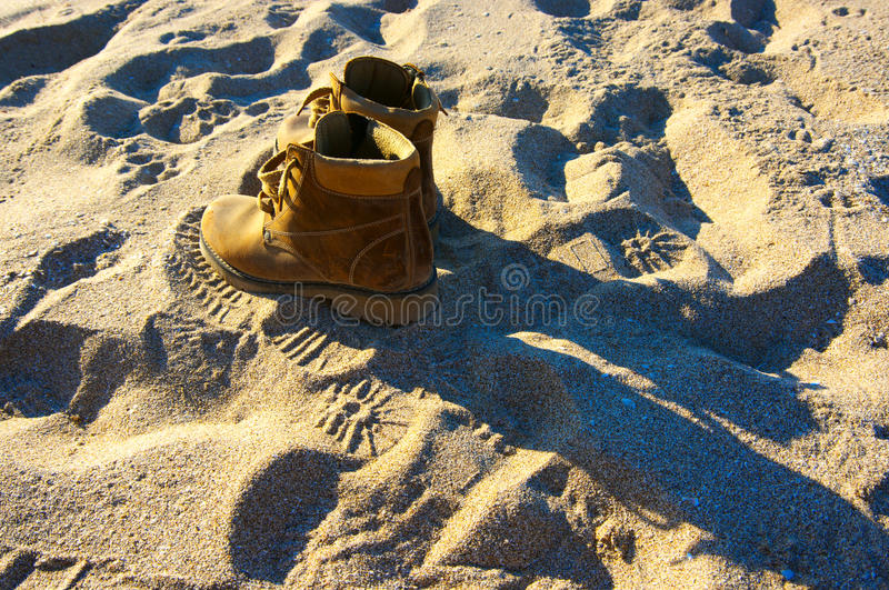 Hiking boots on sand. Shabby yellow leather hiking boots on sand at sunset stock photo