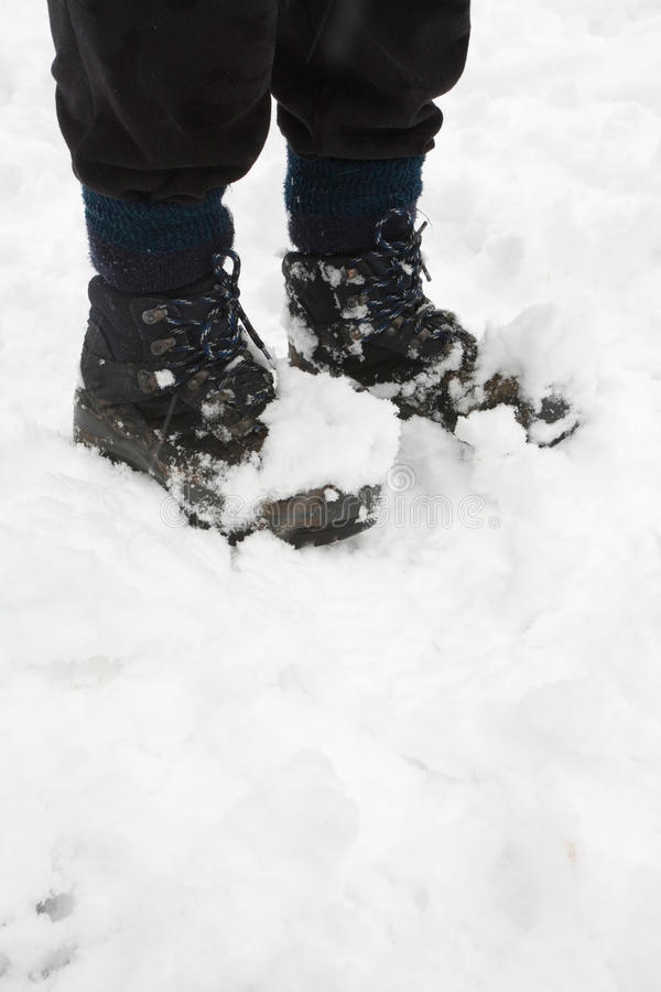 Hiking boots in snow. Womans hiking boots covered in snow, closeup with copy space royalty free stock photo