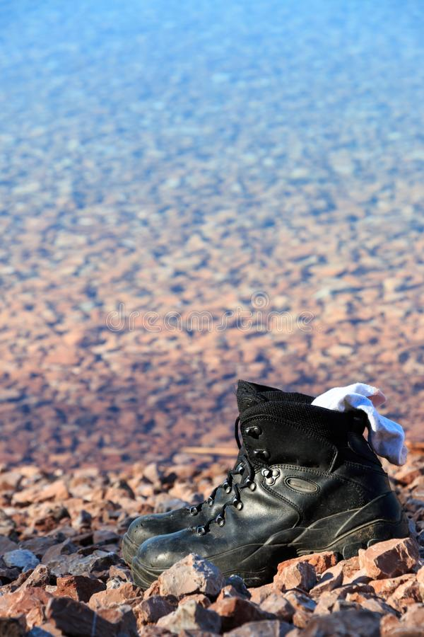 Hiking boots. With socks on the side of a lake stock photography