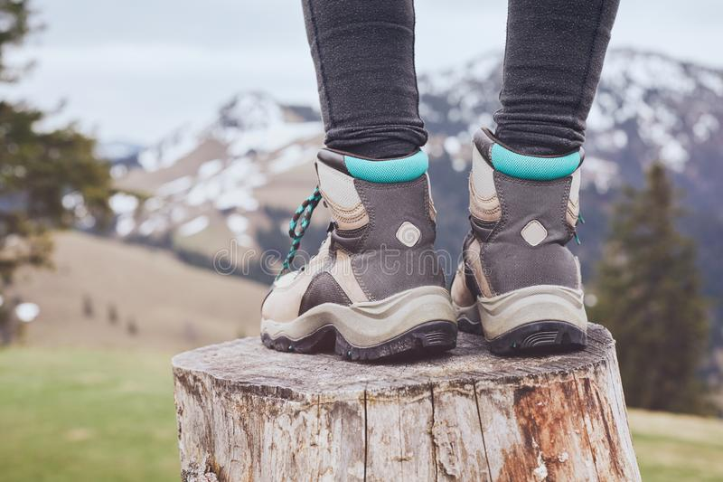 Hiking boots on stump. Close up of female classic leather hiking boots wearing by woman standing on stump in mountains - travel and outdoor activities concept royalty free stock photos