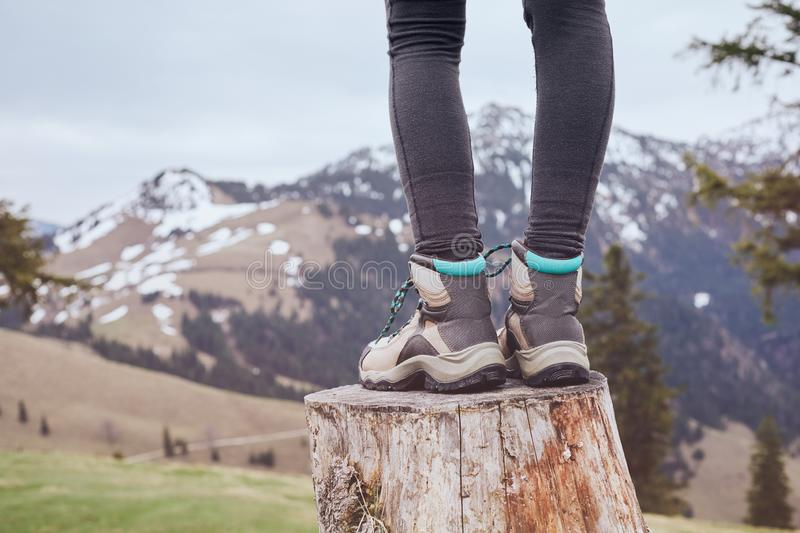 Hiking boots on stump. Close up of female classic leather hiking boots wearing by woman standing on stump in mountains - travel and outdoor activities concept stock image