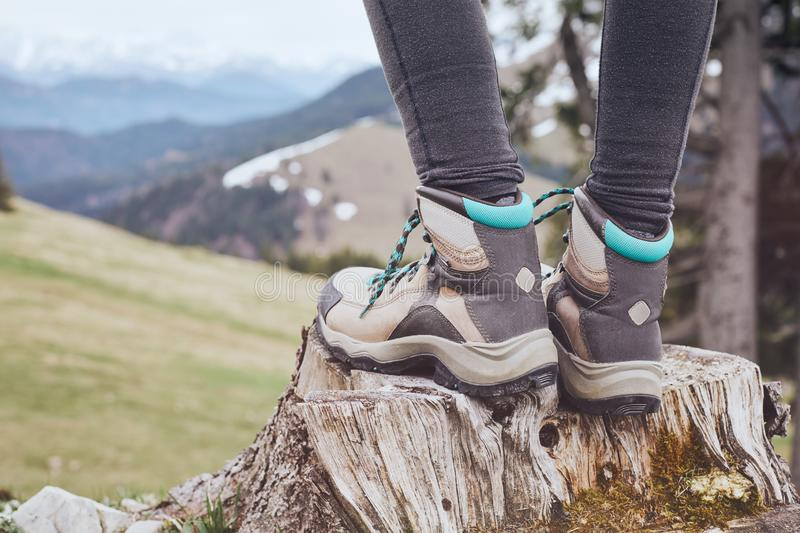 Hiking boots on stump. Close up of female classic leather hiking boots wearing by woman standing on stump in mountains - travel and outdoor activities concept stock photo