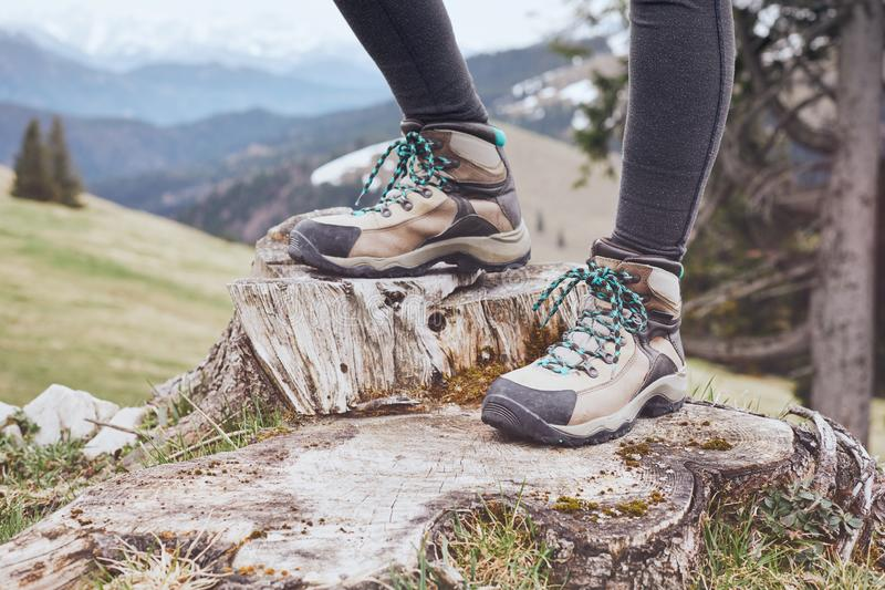 Hiking boots on stump. Close up of female classic leather hiking boots wearing by woman standing on stump in mountains - travel and outdoor activities concept royalty free stock photography