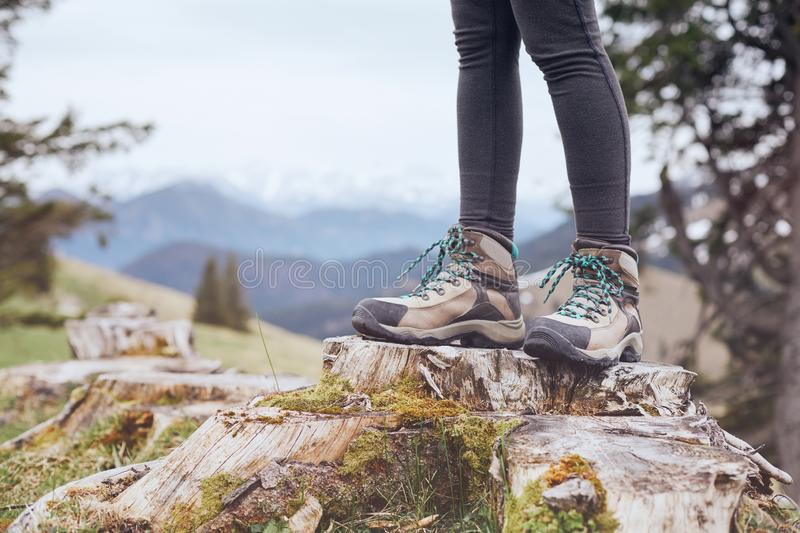 Hiking boots on stump. Close up of female classic leather hiking boots wearing by woman standing on stump in mountains - travel and outdoor activities concept stock photography