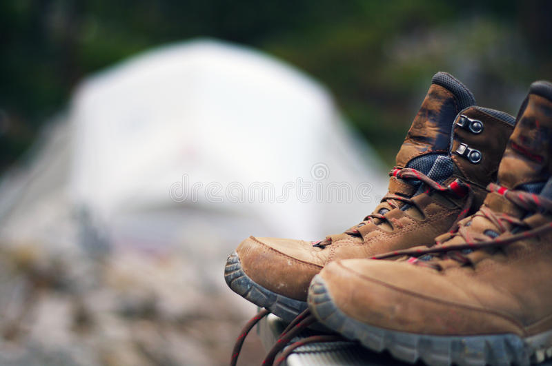 Hiking boots with tent. Hiking boots in focus with tent royalty free stock photo