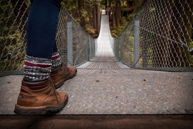 Hiking boots at the top of a suspension bridge in a forest. Hiking boots at the top of a suspension bridge in a forest royalty free stock photography