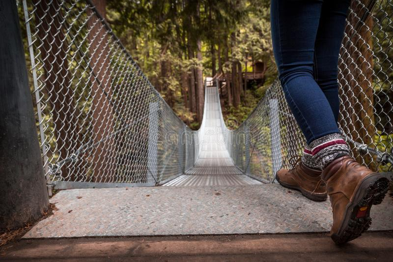 Hiking boots at the top of a suspension bridge in a forest. Hiking boots at the top of a suspension bridge in a forest royalty free stock photos