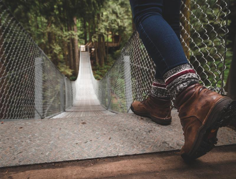 Hiking boots at the top of a suspension bridge in a forest. Hiking boots at the top of a suspension bridge in a forest stock photos