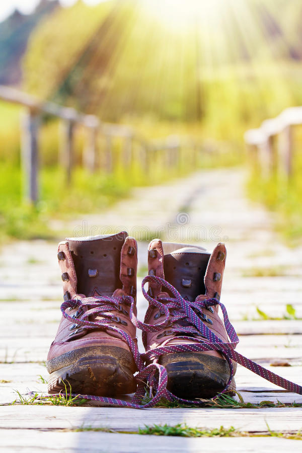 Hiking boots on a way. Hiking boots on a sunny way royalty free stock image