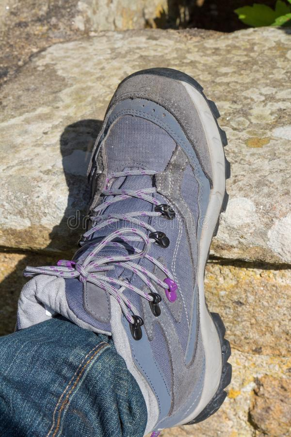 Hiking boots. Of a woman on the stone of a wall stock photography