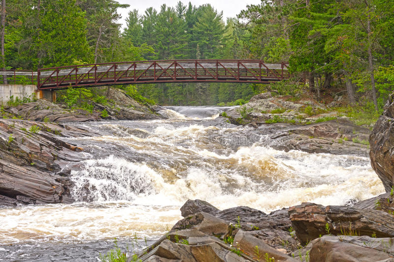 Hiking Bridge over a Wild River stock images