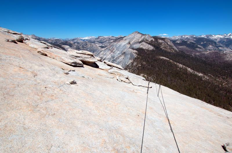 Hiking cables and High Sierras as seen from the top of Half Dome in Yosemite National Park in California USAH royalty free stock photos