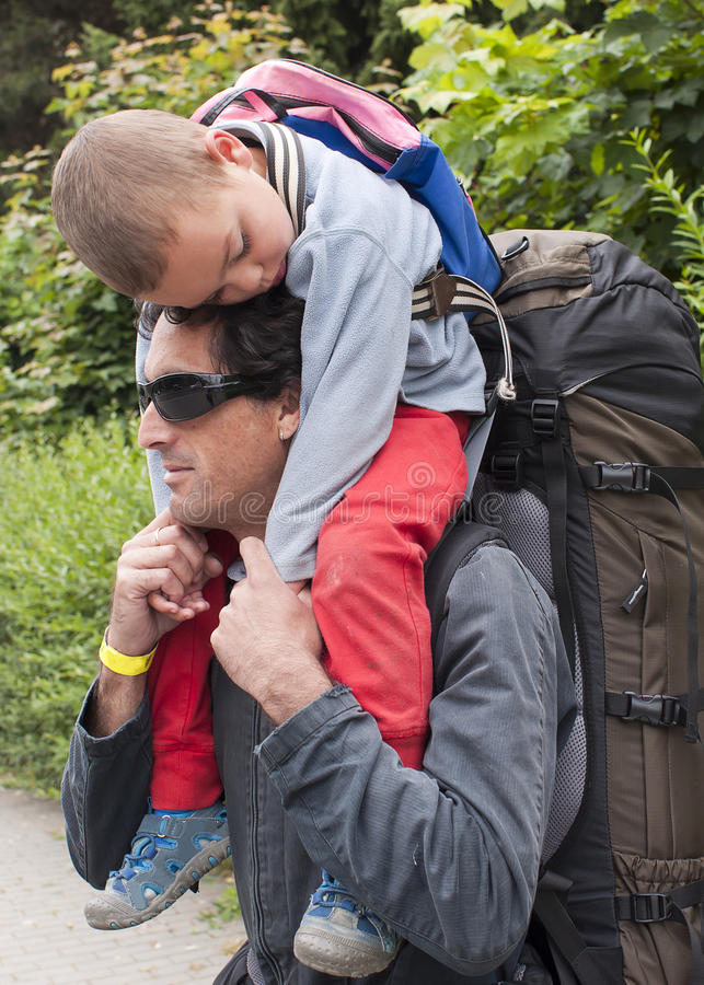Hiking with child, father carrying sleeping child stock image