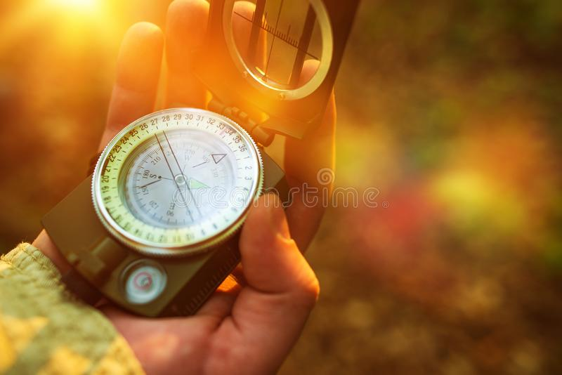Hiking with Compass. Hiking with Small Compass Device. Compass in a Hand stock images